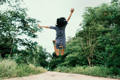 Счастливая девушка скача на путь в древесинах Стоковое Изображение