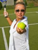 Счастливая девушка стоит с ракеткой на суде на солнечном летнем дне Стоковое Фото