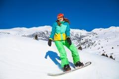 Счастливая девушка стоя на сноуборде в горах стоковые изображения