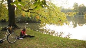 Счастливая девушка студента ослабляя на книге чтения травы в общественном парке осени Велосипед на заднем плане видеоматериал