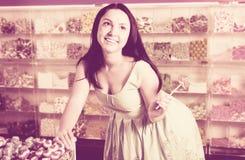 Счастливая девушка с леденцом на палочке на магазине конфет Стоковое фото RF