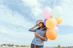 Счастливая девушка с красочными воздушными шарами, в лугах Стоковое Фото