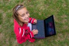 Счастливая девушка с усмехаться компьтер-книжки внешний Стоковые Изображения RF