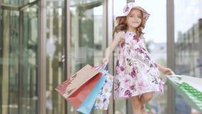 Счастливая девушка с яркими покрашенными сумками поворачивает и наслаждается ходить по магазинам около торгового центра видеоматериал