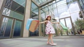 Счастливая девушка с яркими покрашенными сумками поворачивает и наслаждается ходить по магазинам около торгового центра акции видеоматериалы