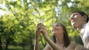 Счастливая девушка фотографирует зеленое дерево сток-видео