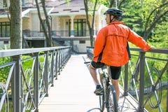 Счастливая езда велосипедиста на дороге в парке города лета Спорт ослабляет концепцию Стоковое Изображение