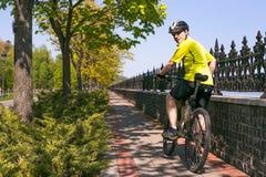 Счастливая езда велосипедиста на дороге в парке города лета Спорт ослабляет концепцию Стоковое Изображение RF