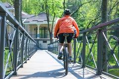 Счастливая езда велосипедиста на дороге в парке города лета Спорт ослабляет концепцию Стоковая Фотография