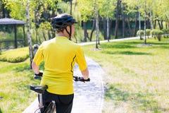 Счастливая езда велосипедиста на дороге в парке города лета Спорт ослабляет концепцию Стоковые Изображения