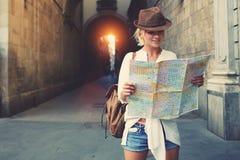 Счастливая женская туристская ища дорога к гостинице на атласе в чужом городе во время каникул Стоковые Фото