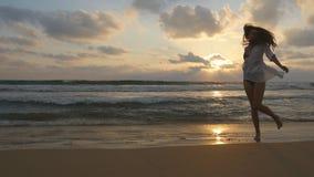 Счастливая женщина бежать и закручивая на пляж около океана Молодая красивая девушка наслаждаясь жизнью и имея потеху на море Стоковое фото RF