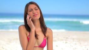Счастливая женщина брюнет говоря на телефоне на пляже сток-видео