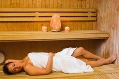 Счастливая женщина брюнет лежа в сауне Стоковая Фотография