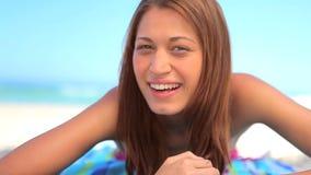 Счастливая женщина брюнет лежа на ее полотенце акции видеоматериалы