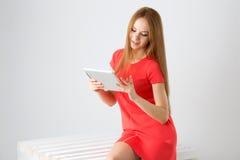 Счастливая женщина брюнет держа в касания пальца компьютера одного сенсорной панели таблетки руки экране и усмехаться электронног Стоковая Фотография RF