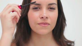 Счастливая женщина брюнет используя тушь сток-видео