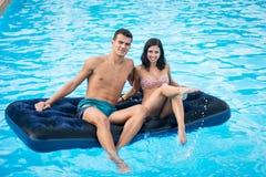 Счастливая женщина брюнет и человек имея потеху на тюфяке на бассейне на их каникулах стоковые фотографии rf