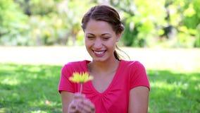 Счастливая женщина брюнет пахнуть желтым цветком сток-видео