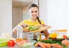 Счастливая женщина варя овощи стоковая фотография rf