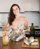 Счастливая женщина варя рыб с ингридиентом Стоковое Фото