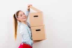 Счастливая женщина двигая в коробки нося дома стоковые фото