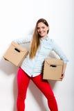 Счастливая женщина двигая в коробки нося дома стоковая фотография