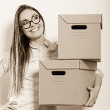 Счастливая женщина двигая в коробки нося дома стоковое фото