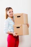 Счастливая женщина двигая в коробки нося дома стоковые изображения