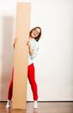 Счастливая женщина двигая в коробку нося квартиры стоковые фото