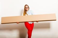 Счастливая женщина двигая в коробку нося квартиры стоковая фотография