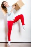 Счастливая женщина двигая в коробку нося дома стоковое фото