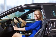 Счастливая женщина внутри автомобиля в автосалоне или салоне Стоковые Фотографии RF