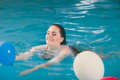 Счастливая женщина в воде имея потеху с воздушными шарами Стоковое фото RF
