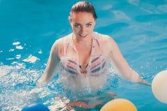 Счастливая женщина в воде имея потеху с воздушными шарами стоковая фотография rf