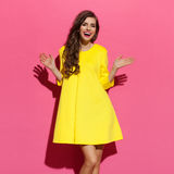 Счастливая женщина в желтом платье при протягиванные оружия стоковые изображения