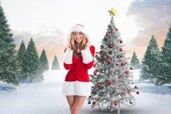 Счастливая женщина в костюме santa стоя против цифров произведенной предпосылки Стоковые Изображения RF