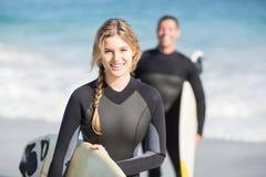 Счастливая женщина в мокрой одежде держа surfboard на пляже Стоковое Изображение