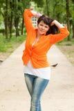 Счастливая женщина в оранжевой куртке стоковые изображения rf