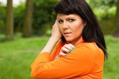 Счастливая женщина в оранжевой куртке стоковое фото rf