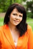 Счастливая женщина в оранжевой куртке стоковая фотография rf