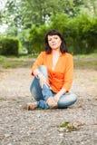 Счастливая женщина в оранжевой куртке стоковое изображение