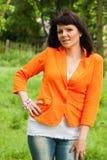 Счастливая женщина в оранжевой куртке стоковые фото