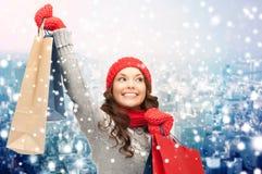 Счастливая женщина в одеждах зимы с хозяйственными сумками стоковое фото