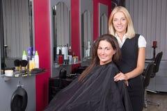 Счастливая женщина в салоне красоты получая отрезок волос Стоковая Фотография