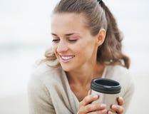 Счастливая женщина в свитере сидя на пляже с чашкой напитка Стоковая Фотография RF