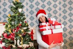 Счастливая женщина в стоге удерживания шляпы santa подарков Стоковые Изображения
