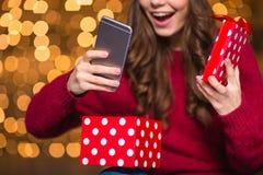 Счастливая женщина в шляпе santa раскрыла настоящий момент и получила smartphone стоковая фотография