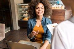 Счастливая женщина говоря с работником в кафе Стоковая Фотография