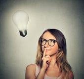 Счастливая женщина девушки думает смотреть вверх на яркой электрической лампочке Стоковая Фотография RF